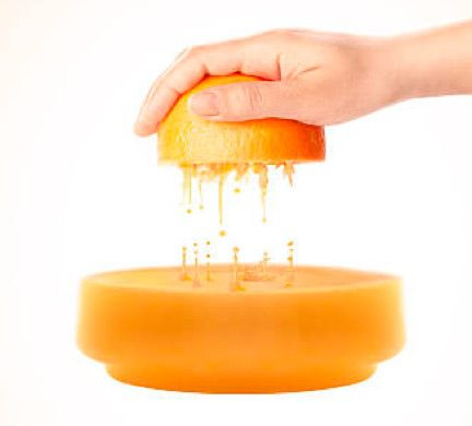 Picture of a hand squizing orange juice